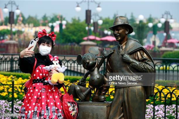 A visitor wearing a face mask takes selfies at Shanghai Disney Resort after the coronavirus pandemic on May 11 2020 in Shanghai China Walt Disney Co...