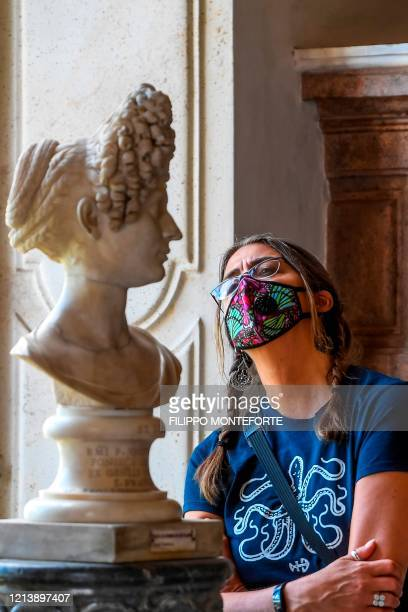 Visitor wearing a face mask views a marble bust of the permanent collection at the Capitoline Museum in Rome as it reopens on May 19, 2020 while the...