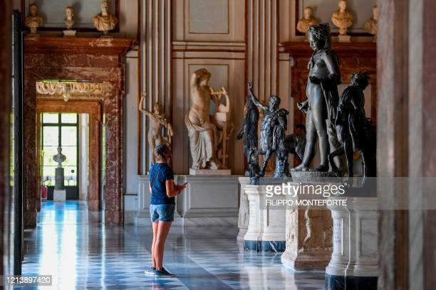 Visitor wearing a face mask views sculptures of the permanent collection at the Capitoline Museum in Rome as it reopens on May 19, 2020 while the...