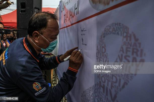 Visitor wearing a facemask signs next to the symbolic Red Ribbon, a recognized symbol for AIDS awareness to commemorate World AIDS Day in Indonesia....