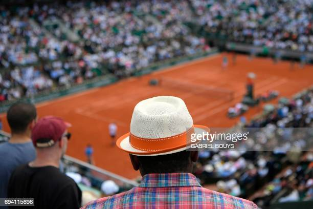 A visitor wearing a hat watches the semifinal tennis match between Switzerland's Stanislas Wawrinka and Britain's Andy Murray at the Roland Garros...