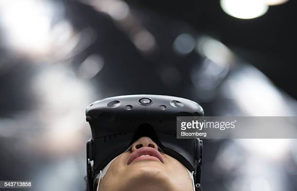 A visitor wearing a HTC Corp Vive headset tries out a virtual reality game during a demonstration by Tokyo VR Startups in Tokyo Japan on Tuesday June...