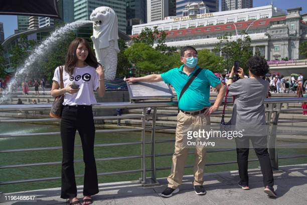 Visitor wearing a mask poses for a photo at the Merlion Park on January 26, 2020 in Singapore. Singapore has confirmed four cases of the deadly...