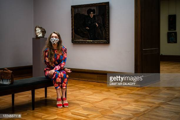 Visitor wearing a protective face mask looks at paintings at the State Tretyakov Gallery as the gallery opened following the easing of measures...