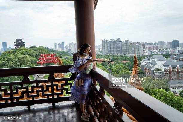 Visitor wearing a protective mask takes a selfie photograph at the Yellow Crane Tower in Wuhan, China, on Saturday, Aug. 8, 2020. More than eight...