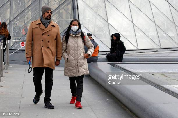 A visitor wearing a protective mask walks in front of the Louvre Museum as the museum was closed for a staff meeting about the coronavirus outbreak...