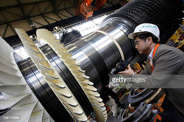 A visitor wearing a Siemens AG hard cap films the rotor coil of a Gas Turbine class H at the German industrial giant Siemens historic construction...