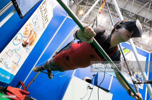 A visitor wearing a virtual reality headset tries a VR attraction at the 4th Live Entertainment EXPO Tokyo at Makuhari Messe on May 31 2017 in Chiba...