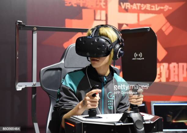Visitor wearing a virtual reality headset tries out a game at Tokyo Game Show in Chiba City, suburban Tokyo on September 21, 2017. Top eSports...
