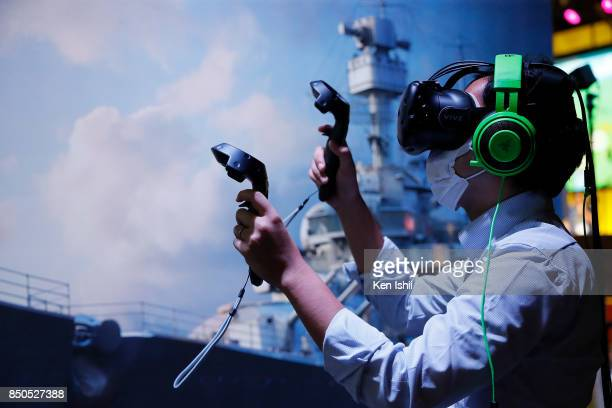 A visitor wearing a VR headset plays a video game in the Wargaming booth during the Tokyo Game Show 2017 at Makuhari Messe on September 21 2017 in...