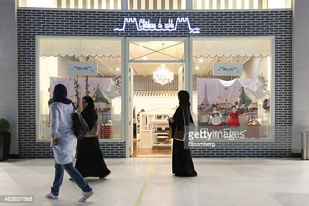 A visitor wearing an hijab browses the window display of a Chateau de Sable children's fashion store in the Dubai Mall operated by Emaar Malls Group...