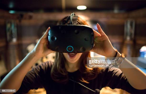 A visitor wearing an HTC Corp Vive VR headset plays a virtual reality video game at the VR Park Tokyo on May 12 2017 in Tokyo Japan The VR Park Tokyo...