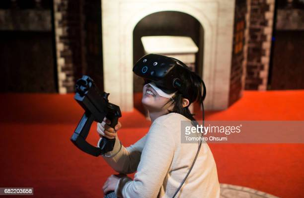 A visitor wearing an HTC Corp Vive VR headset plays the Ghost Attackers VR virtual reality video game at the VR Park Tokyo on May 12 2017 in Tokyo...