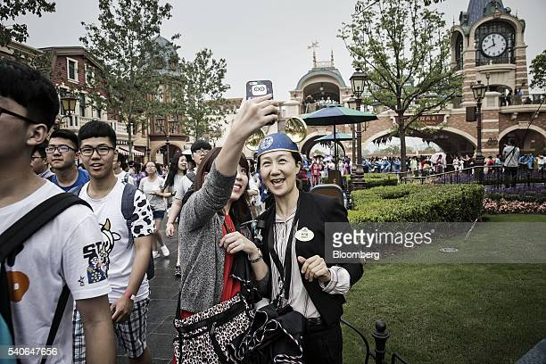 A visitor wearing gold Mickey Mouse ears poses for a selfie photograph during the opening day of Walt Disney Co's Shanghai Disney Resort in Shanghai...