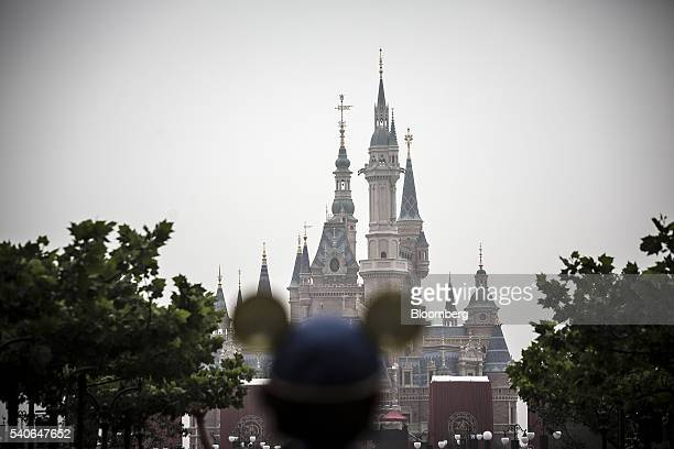 A visitor wearing Mickey Mouse ears stands in front of the Enchanted Storybook Castle during the opening day of Walt Disney Co's Shanghai Disney...