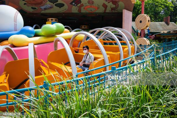 A visitor wearing protective face mask sits on a ride at Walt Disney Co's Disneyland Resort on June 18 2020 in Hong Kong China