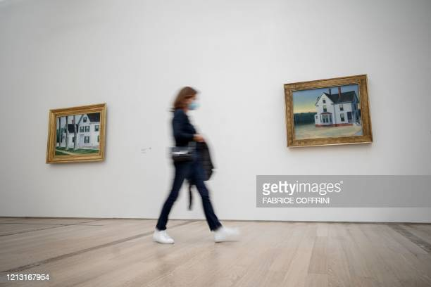 A visitor wearing protective face masks walks next paintings by US painter Edward Hopper entitled Two Puritans and Cape Cod Sunset after the...