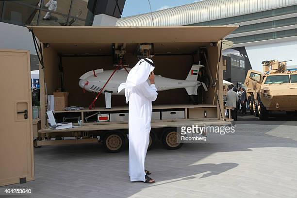 A visitor wearing stands beside an Al Sabr unmanned aerial vehicle manufactured by Abu Dhabi Autonomous Systems Investements on display at the...