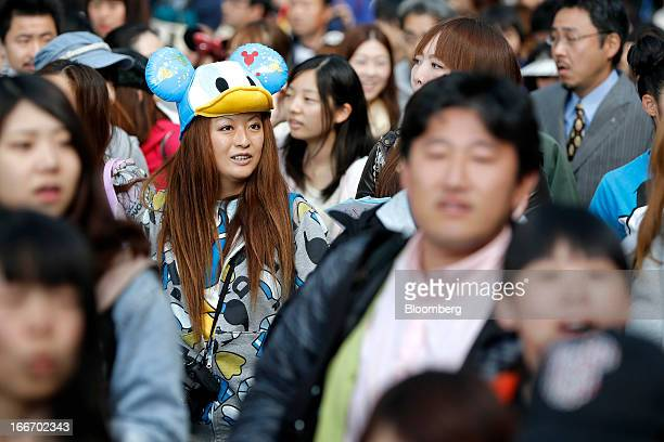 A visitor wears a hat featuring the Walt Disney Co character Donald Duck as she walks through Tokyo Disneyland operated by Oriental Land Co in...