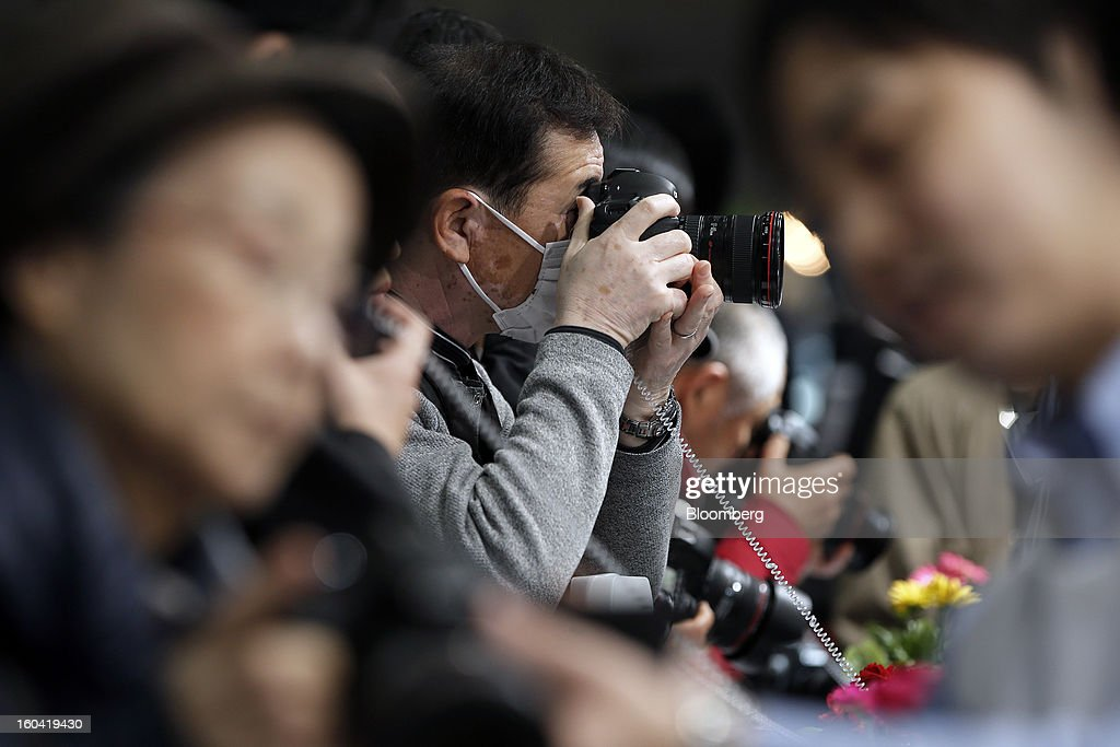 A visitor wears a surgical mask as he tests a Canon Inc. digital single lens reflex (DSLR) camera at the CP+ Camera and Photo Imaging Show in Yokohama City, Japan, on Thursday, Jan. 31, 2013. The CP+ Camera and Photo Imaging Show runs from Jan. 31 to Feb. 3. Photographer: Kiyoshi Ota/Bloomberg via Getty Images
