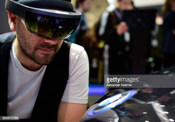 A visitor wears a Virtual Reality goggle next to an electrical BMW i8 car at the Intel stand at the CeBIT 2017 Technology Trade Fair on March 20 2017...
