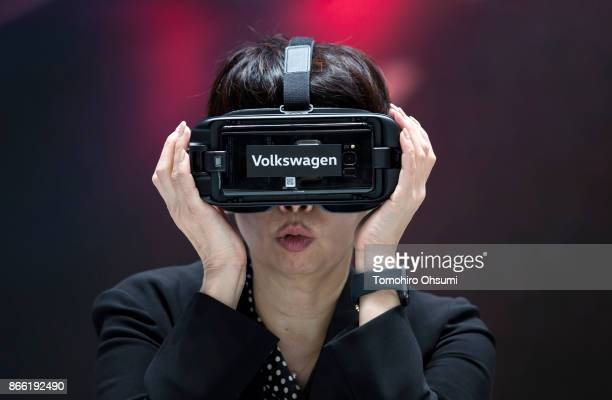 A visitor wears a virtual reality headset inside the Volkswagen AG booth during the Tokyo Motor Show at Tokyo Big Sight on October 25 2017 in Tokyo...