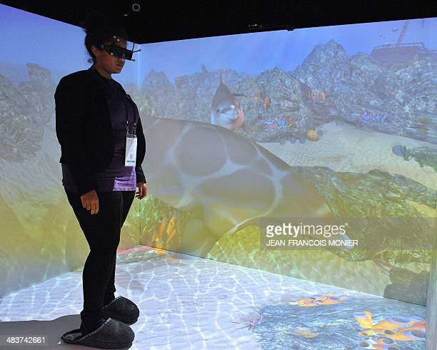 A visitor wears screen glasses as she stands in a virtual aquarium on April 9 at the 16th edition of the Laval Virtual an international meeting on...
