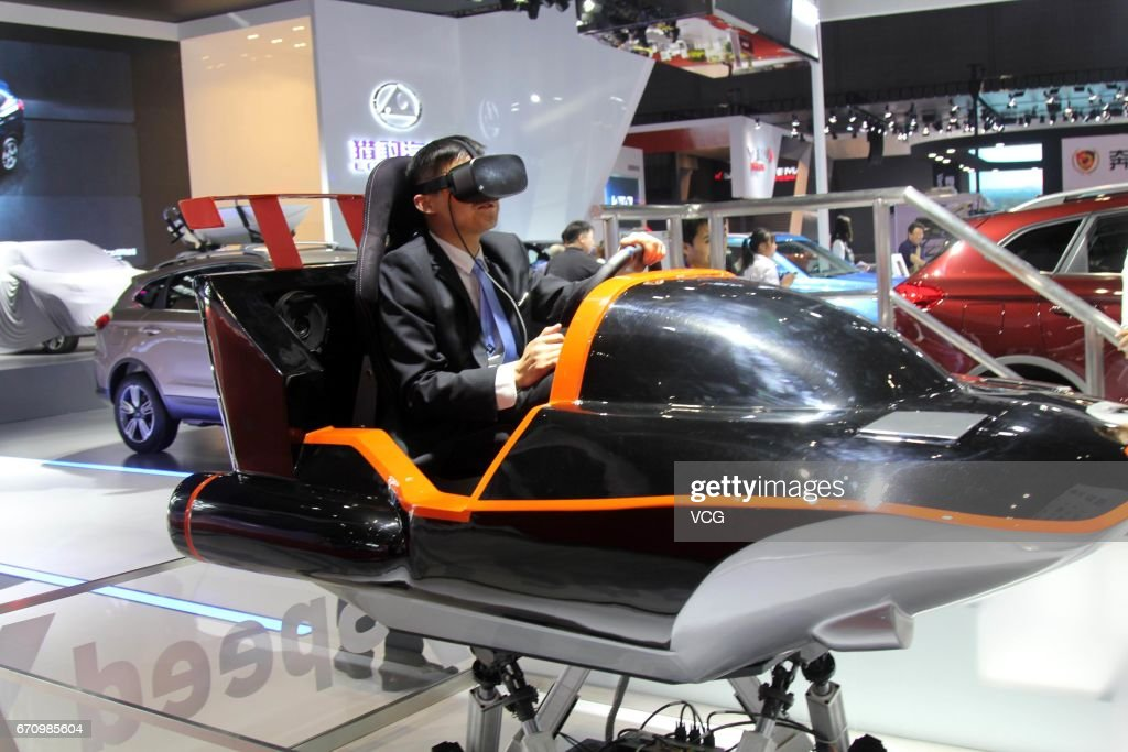 A visitor wears virtual reality (VR) devices to experience virtual driving during the media day of 17th Shanghai International Automobile Industry Exhibition on April 20, 2017 in Shanghai, China. The 17th Shanghai International Automobile Industry Exhibition will be held at National Exhibition and Convention Center (Shanghai) from April 21 to April 28.