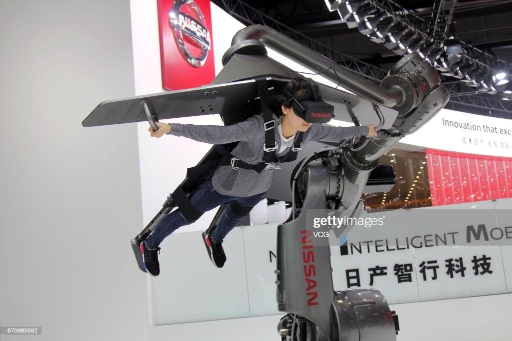 A visitor wears virtual reality (VR) devices to simulate flying experience during the media day of 17th Shanghai International Automobile Industry Exhibition on April 20, 2017 in Shanghai, China. The 17th Shanghai International Automobile Industry Exhibition will be held at National Exhibition and Convention Center (Shanghai) from April 21 to April 28.