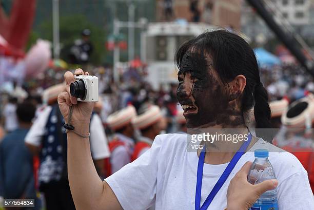 A visitor who is daubed rice ash on face takes photos during the Face Painting Festival in Puzhehei Resort of Qiubei County on July 18 2016 in...