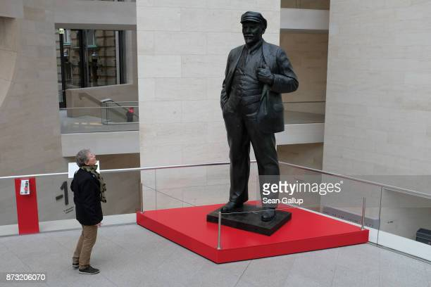 A visitor who said she did not mind being photographed looks at a statue of Russian revolutionary Vladimir Lenin at the German Historical Museum on...