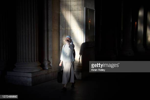 Visitor with a face mask walks through one of the passage ways of the Louvre Museum, Paris, where wearing a face mask in public is compulsory since...