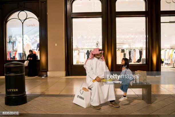 A visitor with a Yahama Motor Co shopping bag sits with a child outside a retail store in Avenues shopping mall in Kuwait City Kuwait on Sunday Aug...