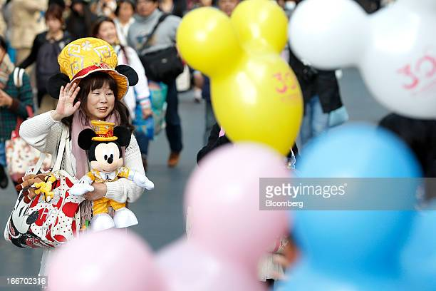 A visitor with Walt Disney Co paraphernalia passes a cluster of balloons as she walks through Tokyo Disneyland operated by Oriental Land Co in...