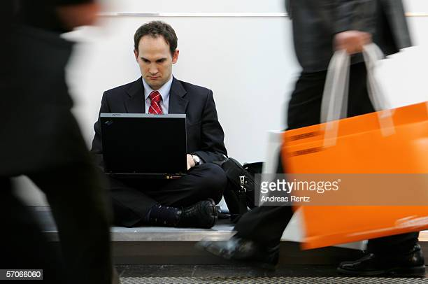 Visitor works on his laptop as people cross him at CeBIT on March 9, 2006 in Hanover, Germany. The world's largest computer and information...
