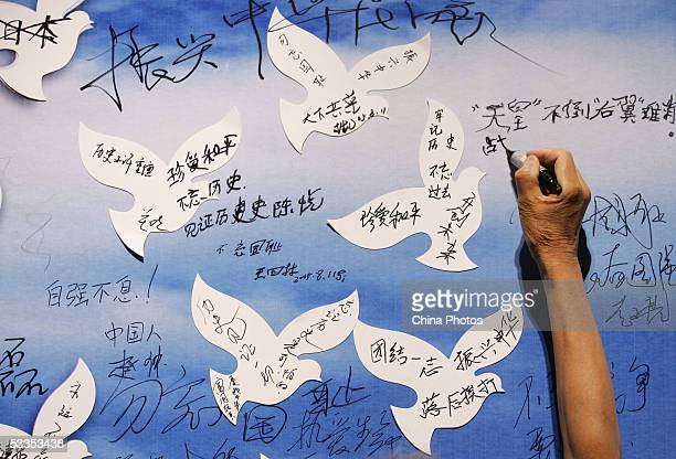 A visitor writes his wishes on a billboard with paper doves during an exhibition on the Nanjing Massacre at the National Museum August 11 2005 in...
