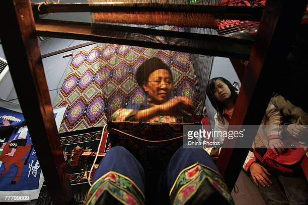 """Visitors admire a folk artist weaving """"Xi Lan Ka Pu"""", a kind of Tujia national brocade, during an exhibition of the Eighth China Arts Festival on..."""