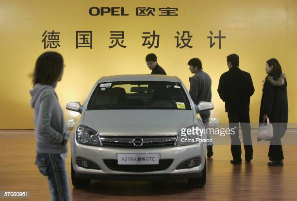 Visitors admire a Opel car at the Imported Auto Expo Shanghai 2006 at the Shanghai Automobile Exhibition Center on March 11, 2006 in Shanghai, China....