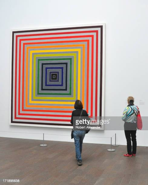Visitors admire a painting by Frank Stella on display at the de Young Museum also known as the MH de Young Memorial Museum in San Francisco...