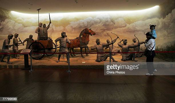Visitors admire chariots in colored lacquer at the Hubei Museum during an exhibition of the Eighth China Arts Festival on November 8 2007 in Wuhan of...