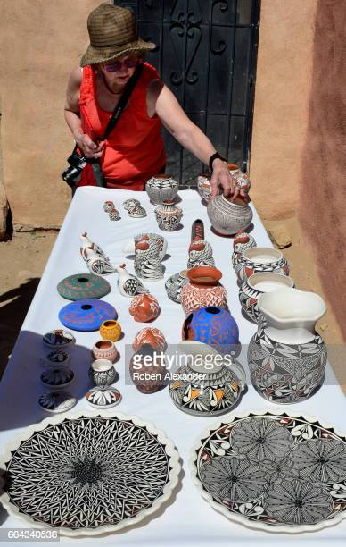 Visitors admire pottery for sale at Sky City one of three Native American villages which make up Acoma Pueblo west of Albuquerque New Mexico The...