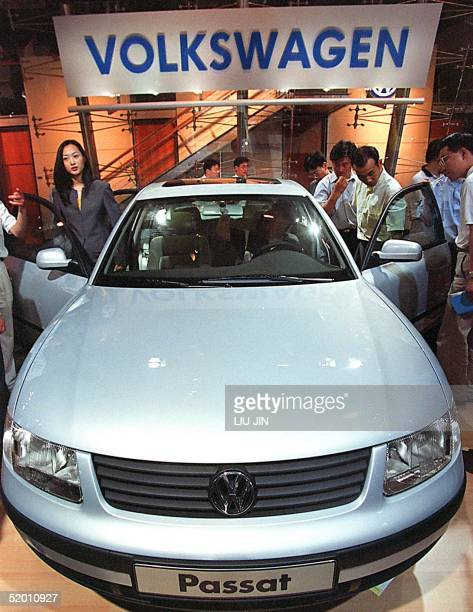 Visitors admire the latest Volkswagen Passat on display at the Auto Shanghai '99 exhibition 16 June 1999. Even in Shanghai where incomes are the...