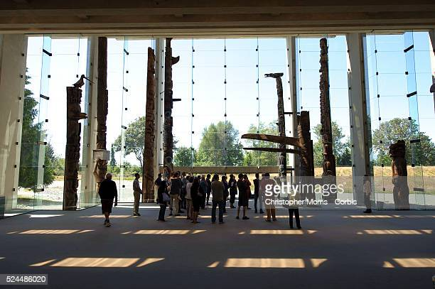 Visitors admire the totem pole carvings on display at the the University of British Columbia's museum of Anthropology, designed by architect Arthur...