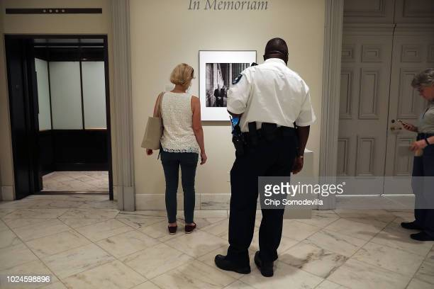 Visitors and a security guard pause to look at a photograph of Sen John McCain on display at the Smithsonian National Portrait Gallery August 27 2018...