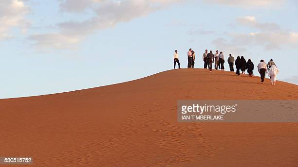 Visitors and Aramco staff climb a dune at Shaybah the base for Saudi Aramco's Natural Gas Liquids plant and oil production in the surrounding Shaybah...