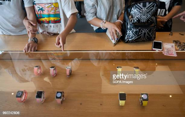 Visitors and buyers study the digital smartwatches called iwatch at the American multinational technology company Apple store in ifc shopping mall in...