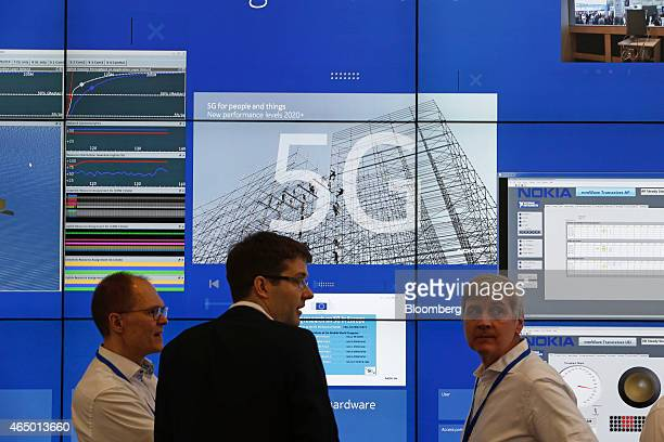 Visitors and employees stand in front of a digital information display about 5G networks for Nokia Solutions and Networks in the Nokia Oyj pavilion...