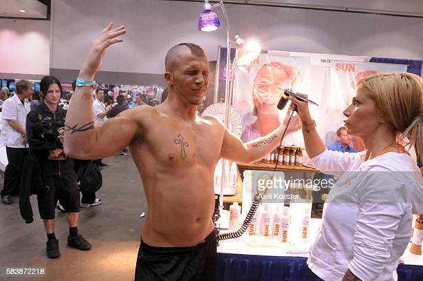Visitors and exhibitors at the Los Angeles FitExpo at the Los Angeles Convention Center Mike Ice receives a sprayon tan from Fernanda Raptis at the...