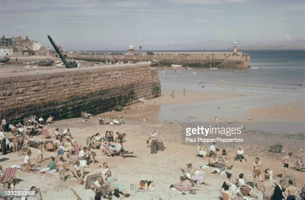 Visitors and holidaymakers seated on deckchairs on the far end of Porthminster Beach located next to the harbour at the seaside town and fishing port...