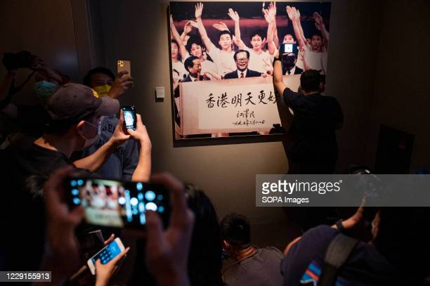 Visitors and media take photos of another visitor making a pro-democracy statement in front of a portrait of former Chinese leader Jiang Zemin at the...